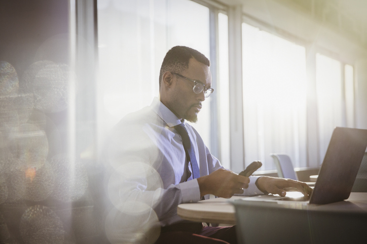 Man at desk on smart phone
