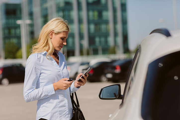 woman standing by car on smartphone